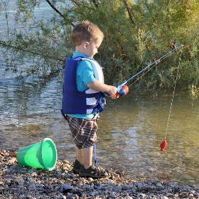 Kid with a fishing rod on a lake