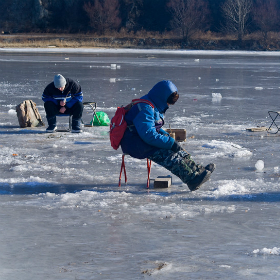 A winter fishing on river. People is fishing the smelt.