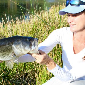 female angler shows off catch after learning about bass fishing for beginners