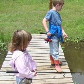 a young boy and girl stand on dock using best fishing rod and reel combo for beginners