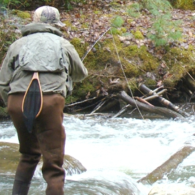 angler fishing in a river using different bottom fishing rigs for trout
