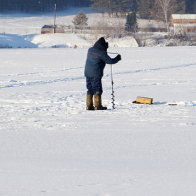 angler making a hole in the ice