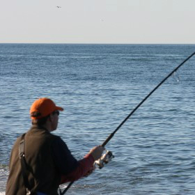 angler practicing surf fishing tips on beach