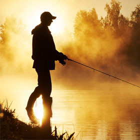 Angler fishing at sunset during best times to fish